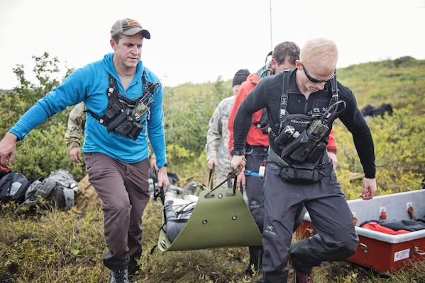 Pararescuemen from the 212th Rescue Squadron, Alaska Air National Guard, and Alaska Army National Guardsmen, move a simulated casualty to their Arctic Sustainment Package during exercise Arctic Chinook, near Kotzebue, Alaska, August 23. Arctic Chinook is a joint U.S. Coast Guard and U.S. Northern Command sponsored exercise which focuses on multinational search and rescue readiness to respond to a mass rescue operation requirement in the Arctic. (U.S. Air National Guard photo by Staff Sgt, Edward Eagerton/released)