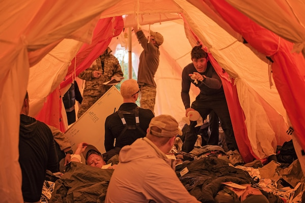 Pararescuemen from the 212th Rescue Squadron, Alaska Air National Guard, triage simulated casualties inside their Arctic Sustainment Package tent during exercise Arctic Chinook, near Kotzebue, Alaska, August 23. Arctic Chinook is a joint U.S. Coast Guard and U.S. Northern Command sponsored exercise which focuses on multinational search and rescue readiness to respond to a mass rescue operation requirement in the Arctic. (U.S. Air National Guard photo by Staff Sgt, Edward Eagerton/released)