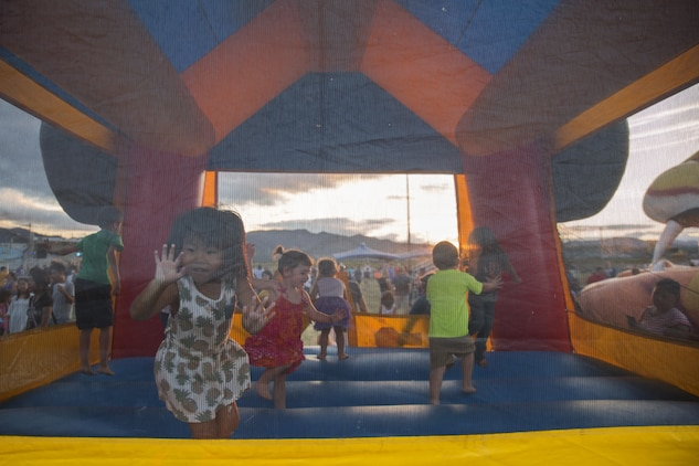Local Japanese and Marine Corps Air Station Iwakuni resident children play in a bounce house during the Summer Music Festival hosted by Marine Corps Community Services at MCAS Iwakuni, Japan, Aug. 27, 2016. Service members, families and local Japanese residents were invited to enjoy a night of free music, food and fun at Penny Lake to come together and celebrate the end of summer. (U.S. Marine Corps photo by Lance Cpl. Donato Maffin)
