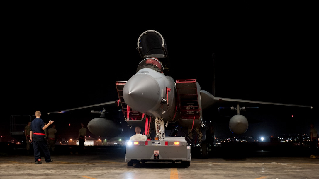 Maintainers assigned to the 67th Aircraft Maintenance Unit maneuver an F-15 Eagle out of an aircraft hangar Aug. 24, 2016, at Kadena Air Base, Japan. Airmen worked during the night to prepare aircraft for a possible typhoon that was postured to hit Okinawa. (U.S. Air Force photo by Senior Airman Peter Reft)