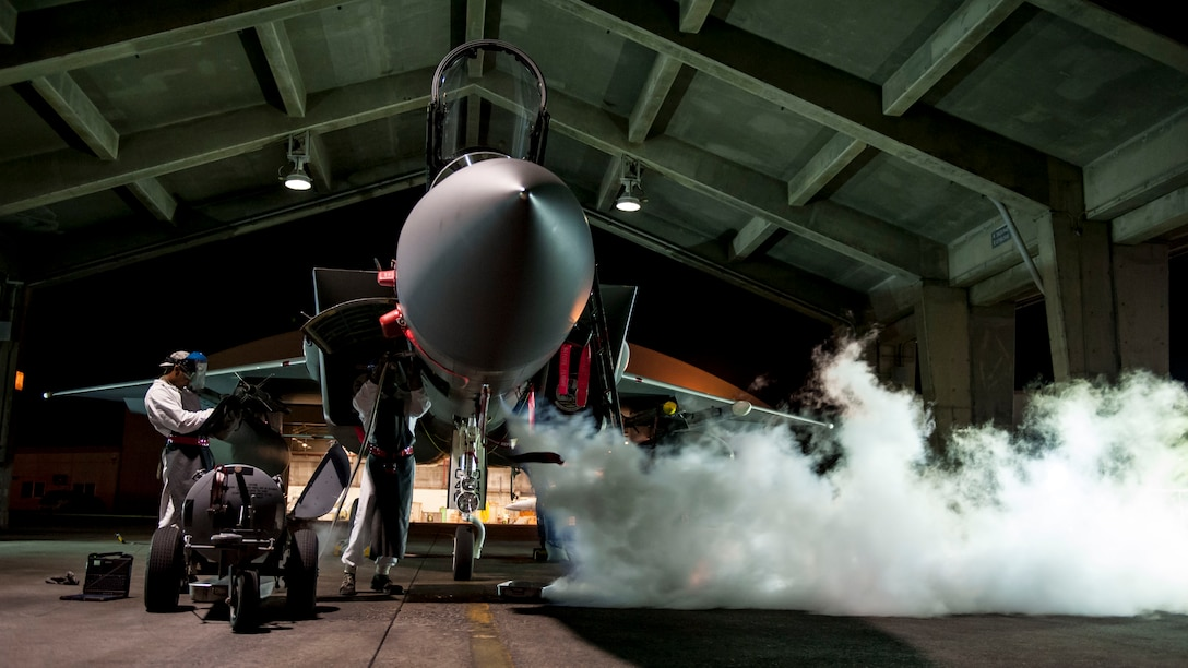 Airman Marquel Marshall and Airman 1st Class Darris Little, 67th Aircraft Maintenance Unit F-15 Eagle crew chiefs, service a liquid oxygen converter on the flightline Aug. 24, 2016, at Kadena Air Base, Japan. Marshal and Little work as swing shift maintainers, ensuring round-the-clock mission readiness of Kadena's F-15s. (U.S. Air Force photo by Senior Airman Peter Reft)