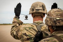 A soldier uses hand and arm signals to guide a UH-60 Black Hawk helicopter participating in slingload training on the Holland drop zone at Fort Bragg, N.C., Aug. 24, 2016. Army photo by Capt. Adan Cazarez