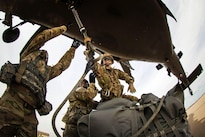 Army Lt. Col. Elizabeth Curtis, right, commander, 407th Brigade Support Battalion, 2nd Brigade Combat Team, successfully attaches a slingload hook onto a UH-60 Black Hawk helicopter during training on the Holland drop zone at Fort Bragg, N.C., Aug. 24, 2016. Army photo by Capt. Adan Cazarez