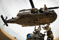 Soldiers attach a slingload hook onto a UH-60 Black Hawk helicopter during training on the Holland drop zone at Fort Bragg, N.C., Aug. 24, 2016. The soldiers are assigned to the XVIII Airborne Corps, Air Assault School. Army photo by Capt. Adan Cazarez