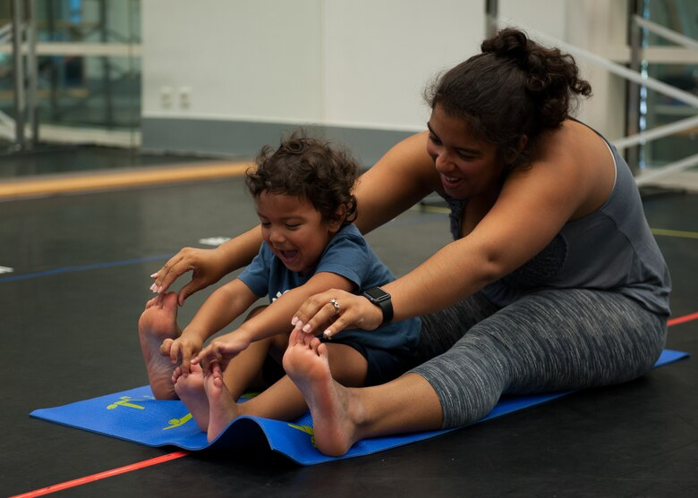 Kadyzshea Barrios and her son, Roy, reach for their toes during a Mommy and Me Yoga class Aug. 29, 2016, at Ramstein Air Base, Germany. This is the first Mommy and Me Yoga class to be offered at Ramstein. (U.S. Air Force photo/ Airman 1st Class Savannah L. Waters)