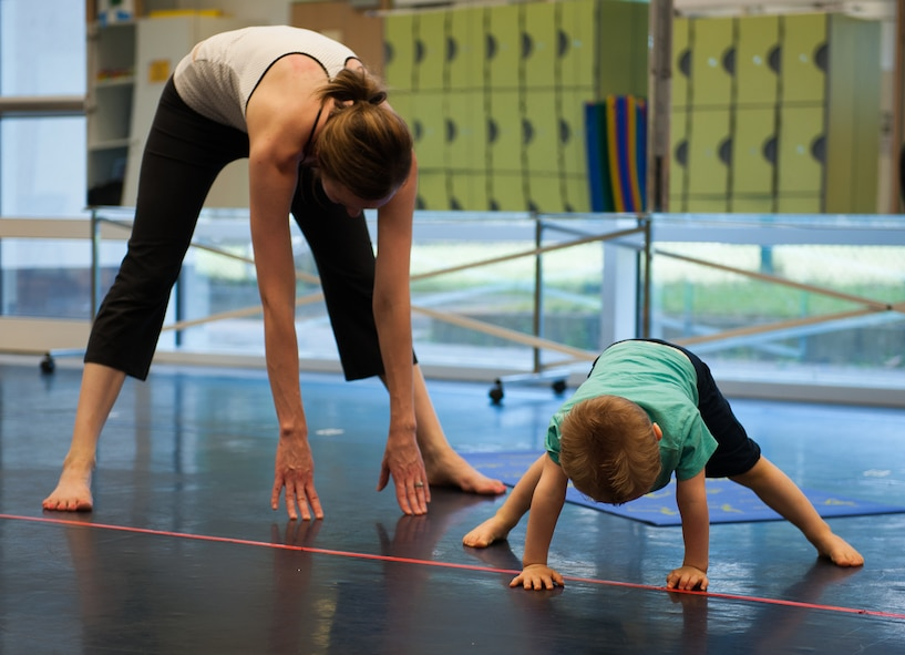 Jackson Parnell joins his mother, Brandy Parnell, in a cool-down stretch during the first Mommy and Me Yoga class Aug. 29, 2016, at Ramstein Air Base, Germany. The instructor incorporated nontraditional names for poses to keep the young children more engaged, as well as created an environment to promote a deeper mother-to-child bond. (U.S. Air Force 