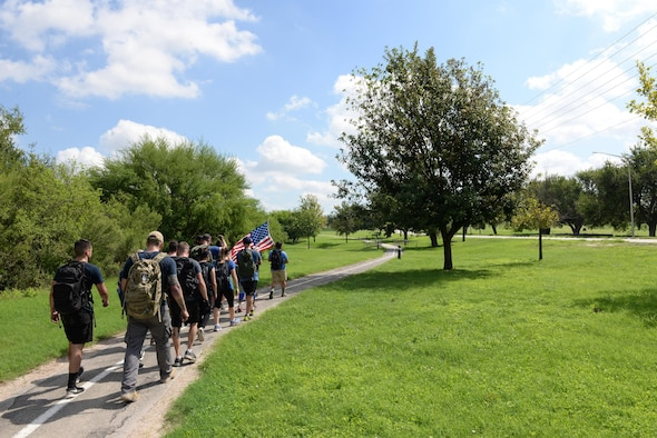 Team Cohesion Challenge participants ruck-march to their mock extraction point on Laughlin Air Force Base, Texas, Aug. 27, 2016. This GORUCK Light event had Laughlin's participants rucking more than seven miles, carrying a 10 to 20 pound rucksack, transporting railroad ties, flipping tires, climbing rockwalls and conquering other physically challenging obstactle to test team work. (U.S. Air Force photo/Airman 1st Class Benjamin N. Valmoja)