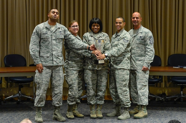 Chief Master Sgt. John Bentivegna (right), 50th Space Wing command chief, presents the Schriever Debate trophy to the 5/6 Council debate team following the first Schriever Debate at Schriever Air Force Base, Colorado, Thursday, Aug. 25, 2016. The 5/6 Council defeated the CGO Council in the first iteration of the new event. (U.S. Air Force photo/Christopher DeWitt)