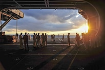 Sailors prepare to assist with a burial-at-sea ceremony aboard the aircraft carrier USS George Washington in the Atlantic Ocean, Aug. 27, 2016. The George Washington is underway conducting carrier qualifications. Navy photo by Petty Officer 2nd Class Kris R. Lindstrom