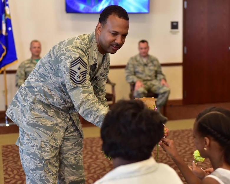 Chief Master Sgt. Kenneth Eason, command chief, 914th Airlift Wing, presents gifts to members of his family during a ceremony at Niagara Falls Air Reserve Station on Aug. 6, 2015. Eason assumes the responsibility of the highest enlisted position in the Wing. (U.S. Air Force photo by Staff Sgt. Richard Mekkri)