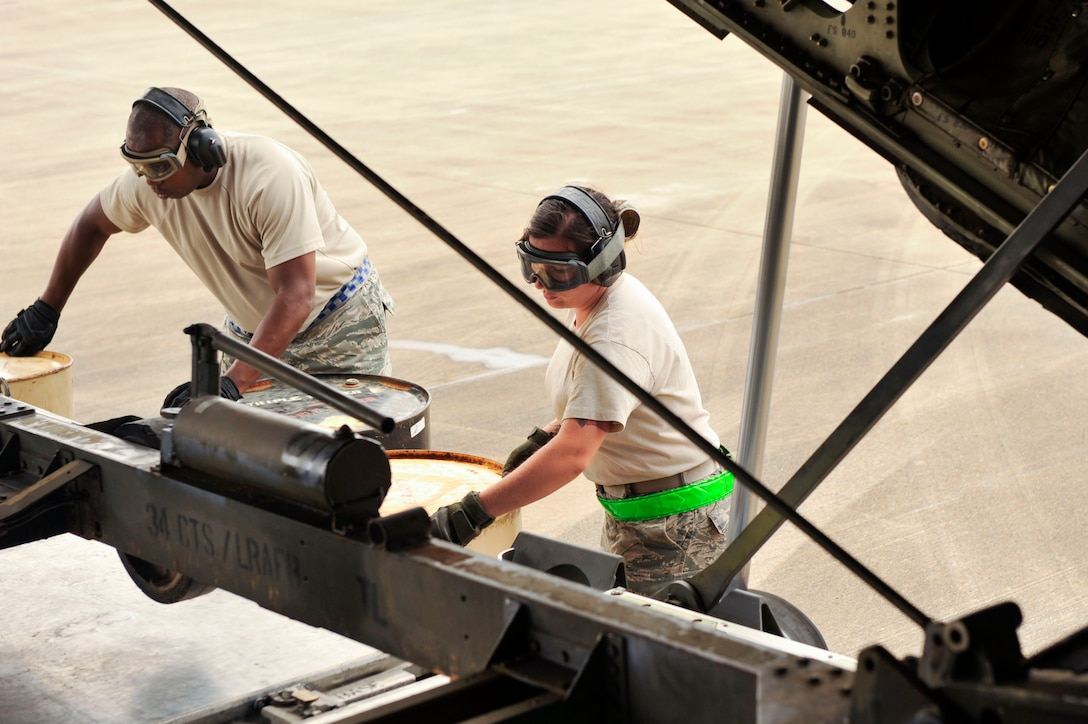 Airmen from the 305th Aerial Port Squadron at Joint Base McGuire-Dix-Lakehurst, New Jersey, load barrels under a trailer carrying a 1,430-lb. C-130 engine stand trailer unit Aug. 26, 2016, at a landing zone in Alexandria, Louisiana. The barrels are used to support the pallet as the C-130 slowly pulls forward to release the equipment. (U.S. Air Force photo by Staff Sgt. Regina Edwards)