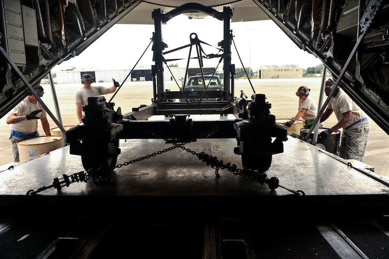 Airmen from the 305th Aerial Port Squadron at Joint Base McGuire-Dix-Lakehurst, New Jersey, uses combat offload method B to remove a C-130 engine stand trailer unit Aug. 26, 2016, at a landing zone in Alexandria, Louisiana. The combat offload method B uses barrels as a foundation for the pallets to hold the trailer as the C-130 slowly moves forward to release the equipment. (U.S. Air force photo by Staff Sgt. Regina Edwards)