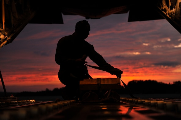 U.S. Air Force Senior Airman Mario Linton, 41st Airlift Squadron loadmaster, ties down the chock as the sun rises before takeoff Aug. 26, 2016, at Little Rock Air Force Base, Ark. The 41st AS trained on different offload techniques and practiced the Combat Offload Method B technique. (U.S. Air Force photo by Staff Sgt. Regina Edwards)