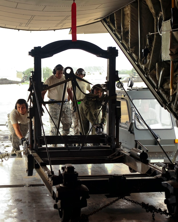 Loadmasters from the 41st Airlift Squadron from Little Rock Air Force Base, Ark., assist Airmen from the 305th Aerial Port Squadron at Joint Base McGuire-Dix-Lakehurst, New Jersey, loading a C-130 engine stand trailer unit Aug. 26, 2016, at a landing zone in Alexandria, Louisiana. The 1,430-lb. trailer is used to safely transport an aircraft's engine from the runway to a maintenance bay to allow more precise repairs. (U.S. Air Force photo by Staff Sgt. Regina Edwards)