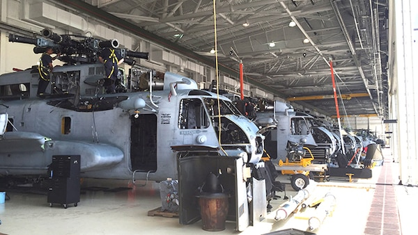 Aircraft maintenance professionals at the Marine Corps Air Station New River RESET support site in Jacksonville, N.C. shown inspecting the main rotor head on an aging MH-53 heavy-lift helicopter. Currently 12 MH-53's require replacement of one sleeve nut on the rotor head and seven on the sleeves and spindles which are the main components for the helicopter's rotary blades. Defense Logistics Agency Aviation Customer Operations Directorate's weapon systems program office in Richmond, Virginia, is part of the management team that helps keep the MH-53 helicopter fleet mission ready.