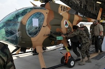 The first of four MD-530F Cayuse attack helicopters is unloaded from a C-17 Globemaster aircraft at Hamid Karzai International Airport in Kabul, Afghanistan, Aug. 25, 2016. Combined Security Transition Command - Afghanistan oversaw the transfer of four MD-530F Cayuse attack helicopters and a C-130H Hercules transport aircraft to the Afghan air force. Navy photo by Lt. Christopher Hanson