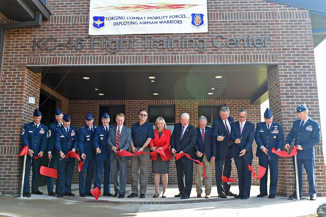 """U.S. Air Force leaders and community partners cut a ribbon during the """"Forging the 46"""" ceremony, Aug. 30, 2016, at Altus Air Force Base, Okla. The event consisted of an assumption of command for the reactivated 56th Air Refueling Squadron, dedication of the new KC-46 training facility, speeches from key Air Force and community leaders and concluded with a tour of the new facility for attendees. (U.S. Air Force photo by Senior Airman Dillon Davis)"""