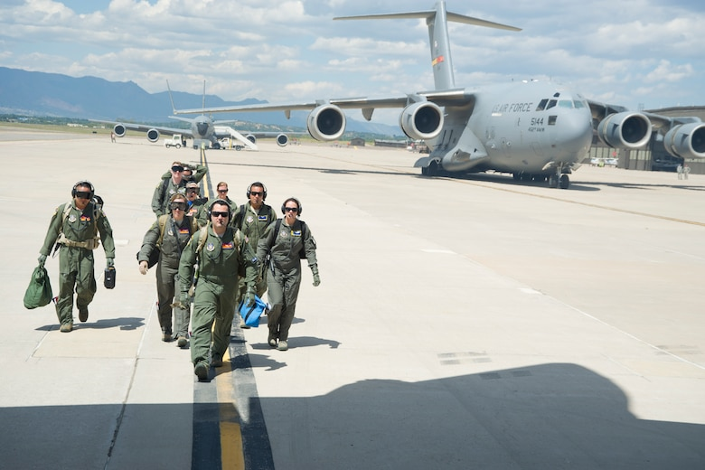 A multi-unit team of aeromedical evacuation squadron members make their way to a C-130H3 Hercules on the Peterson Air Force Base, Colorado, flight line Saturday, Aug. 27, 2016, to conduct in-flight training. More than a dozen 459th AES flight nurses, technicians and administrators flew to Peterson to conduct joint unit training with other AE squadrons on board the KC-135R Stratotanker, C-17 Globemaster III and C-130H3 Hercules. (U.S. Air Force photo/Staff Sgt. Kat Justen)