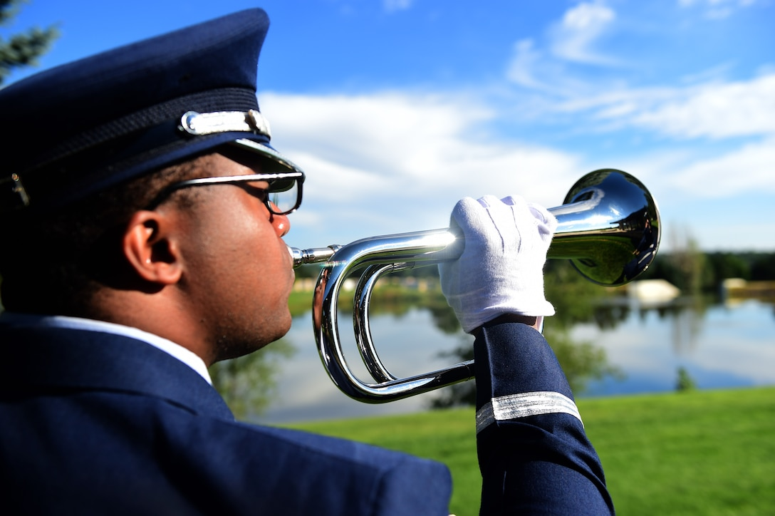 Senior Airman James Cunningham, U.S. Air Force Mile High Honor Guard member, plays taps on a bugle during a funeral August 30, 2016, at Fort Logan National Cemetery, Colo. Taps received its name in 1874, but was made the official Army Bugle call after the Civil War. (U.S. Air Force photo by Airman 1st Class Gabrielle Spradling/Released)