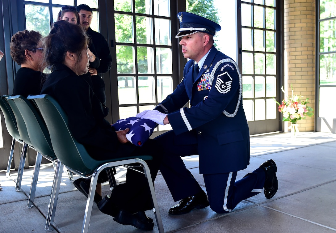 Master Sgt. Wolfram Stumpf, U.S. Air Force Mile High Honor Guard member, presents a widow an American flag during the funeral for her husband August 30, 2016, at Fort Logan National Cemetery, Colo. The American flag is presented during a military honors funeral as a lasting tribute to the veteran's family. (U.S. Air Force photo by Airman 1st Class Gabrielle Spradling/Released)
