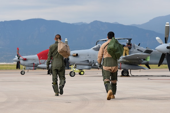 PETERSON AIR FORCE BASE, Colo. – An Afghanistan air force pilot, right, joins his trainer for a morning sortie of high-density altitude training in an A-29 Super Tucano aircraft at Peterson Air Force Base, Colo., Aug. 24, 2016. The Afghanis are participating in a program training 30 pilots and 90 maintainers for the aircraft, which will be used mainly for close air support functions. (U.S. Air Force photo by Airman 1st Class Dennis Hoffman)