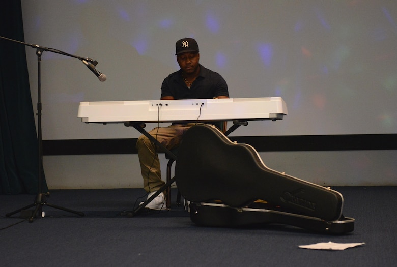 Airman 1st Class Blake Brooks, 36th Medical Operations Squadron public health technician, plays the keyboard during a Women's Equality Day event Aug. 26, 2016, at Andersen Air Force Base, Guam. The event was held to commemorate the ratification of the 19th amendment and showcased a number of performances. (U.S. Air Force photo by Airman 1st Class Arielle Vasquez/Released)