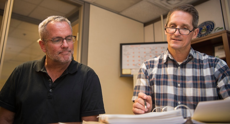 Jim Bailey, Denton logistics manager (left), cross checks the upcoming mission details with Ken Hundemer, Denton operations manager (right), in the Denton program office on Joint Base Charleston – Air Base, S.C., Aug. 30, 2016. The Denton program works with nonprofit organizations to send medical equipment and supplies, nonperishable foods, education materials, hygienic supplies and vehicles to countries in need around the world. (U.S. Air Force photo/Airman 1st Class Thomas T. Charlton)
