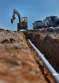 A construction worker with Atlantic Electric LLC digs a trench for a pipe at the North Auxiliary Airfield in North, South Carolina, Aug. 25, 2016. The airfield directly supports the 437th and 315th Airlift Wing's C-17 Globemaster III aircrew training and proficiency training. (U.S. Air Force Photo/Airman Megan Munoz)