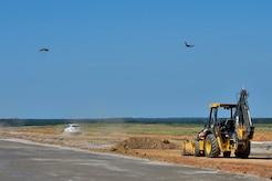 A C-17 Globemaster II aircraft drops cargo at the North Auxiliary Airfield in North, South Carolina, while a stone base is laid down for a new landing zone, Aug. 25, 2016. The airfield directly supports the 437th and 315th Airlift Wing's C-17 aircrew and proficiency training. (U.S. Air Force Photo/Airman Megan Munoz)