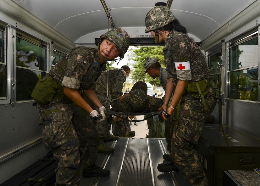 Republic of Korea air force airmen and 51st Medical Group medics raise a simulated bombing victim into a medical transportation bus during a joint mass-casualty medical exercise at Osan Air Base, Republic of Korea, Aug. 22, 2016. The two groups of medics worked side-by-side to triage and transport the simulated victims to proper medical facilities as well as exchange techniques and advice. (U.S. Air Force photo by Senior Airman Victor J. Caputo)