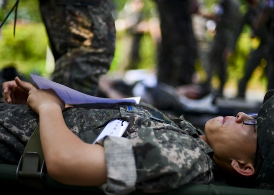 A Republic of Korea air force airman simulates waiting for treatment during a joint mass-casualty medical exercise at Osan Air Base, Republic of Korea, Aug. 22, 2016. ROKAF medical personnel worked with 51st Medical Group medics on triaging and transporting victims of a simulated bombing to proper medical facilities. (U.S. Air Force photo by Senior Airman Victor J. Caputo)