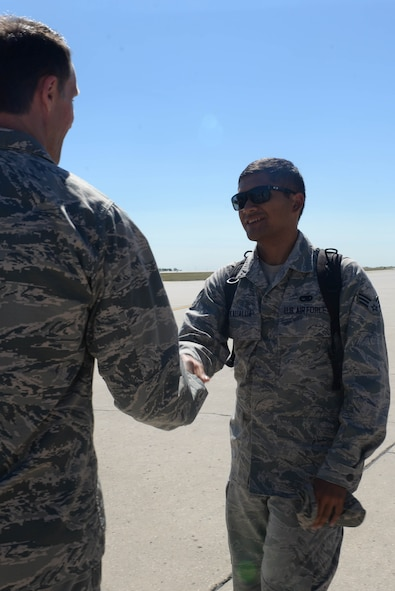 Senior Airman Kawika Kekaualua, an Airman assigned to the 5th Aircraft Maintenance Squadron, is greeted by Col. Matthew Brooks, 5th Bomb Wing commander, after returning home from deployment at Minot Air Force Base, N.D., Aug. 29, 2016. Over 300 Airmen were welcomed by base leadership, family and friends. (U.S. Air Force Photo/Airman 1st Class Jessica Weissman)