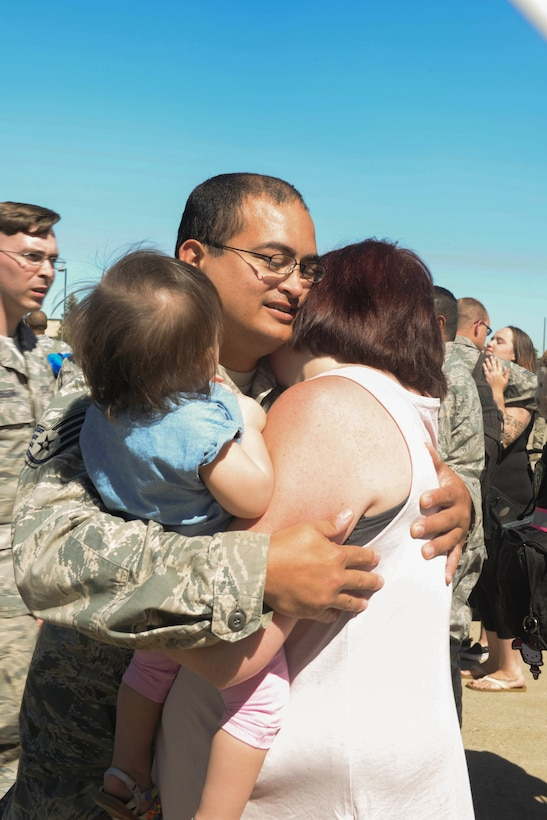 Staff Sgt. Michael McCarty, an Airman assigned to the 5th Munitions Squadron, reunites with his family at Minot Air Force Base, N.D., Aug. 29, 2016. Various Minot AFB Airmen were deployed to Andersen AFB, Guam, in support of the continuous bomber presence. (U.S. Air Force Photo/Airman 1st Class Jessica Weissman)
