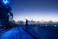 Navy Petty Officer 3rd Class Joseph Lieby awaits incoming aircraft on the flight deck of the amphibious assault ship USS Boxer in the Pacific Ocean, Aug. 26, 2016. Lieby is an aviation boatswain's mate handling. Boxer, flagship for Boxer Amphibious Ready Group, 13th MEU team, is operating in the U.S. 3rd Fleet area of operations. Navy photo by Petty Officer 3rd Class Michael T. Eckelbecker