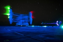A plane director signals to the crew of a Marine Corps MV-22 Osprey aircraft during night operations on the flight deck of the amphibious assault ship USS Boxer in the Pacific Ocean, Aug. 26, 2016. Navy photo by Petty Officer 3rd Class Michael T. Eckelbecker