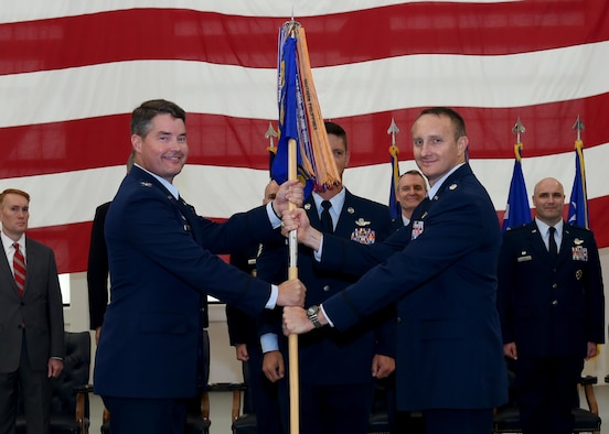 "U.S. Air Force Col. Bryan Wood [left], 97th Operations Group commander, passes the guidon for the 56th Air Refueling Squadron to U.S. Air Force Lt. Col. Daniel Ruttenber [right], 56th ARS commander, during the ""Forging the 46"" ceremony, Aug. 30, 2016, at Altus Air Force Base, Okla. The event consisted of an assumption of command for the reactivated 56th ARS, dedication of the new KC-46 training facility, speeches from key Air Force and community leaders and concluded with a tour of the new facility for attendees. (U.S. Air Force photo by Airman 1st Class Kirby Turbak/Released)"