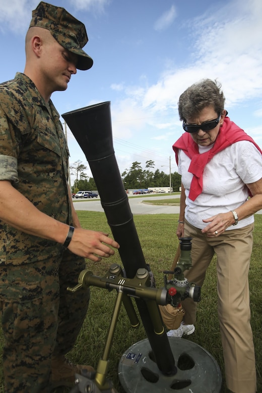 A Marine with 2nd Battalion, 6th Marine Regiment, 2nd Marine Division explains how the a weapon works to a family member of a 1st Bn, 6th Marine veteran, visiting at Camp Lejeune, N.C., Aug. 29, 2016. 1/6 organized a reunion for the survivors of a helicopter crash involving 1/6 while they were attached to the 22nd Marine Expeditionary Unit in 1986.  (U.S. Marine Corps photo by Lance Cpl. Miranda Faughn)