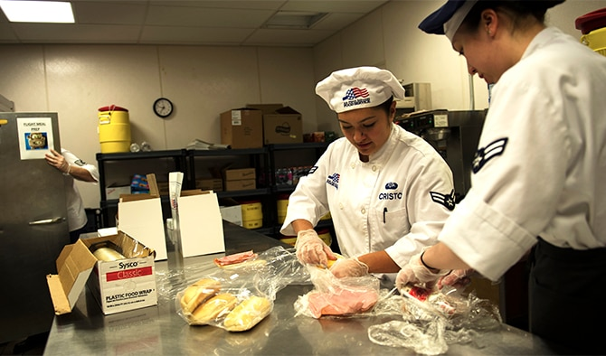 Airman 1st Class Tiffany Cristo, 92nd Force Support Squadron food services apprentice, and Airman 1st Class Marina Ericson, 92nd FSS food services apprentice, prepare food for boxed meals, Aug. 24, 2016, at Fairchild Air Force Base. The flight kitchen offers an online order form through the base's SharePoint, so Airmen can see what foods are available and place an order. (U.S. Air Force photo/Airman 1st Class Sean Campbell)