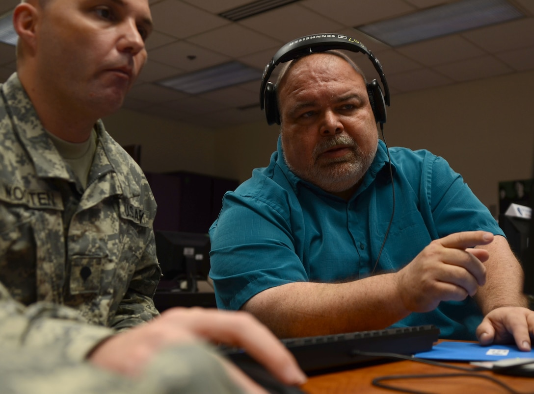 Bob Beyer, the team lead of the radio segment of the Broadcast Communication Specialist course at the Defense Information School on Fort Meade, coaches Army Spc. Richard Wooten, a student in the course, Aug. 16, 2016, at the school. Beyer was recognized recently as the DINFOS Civilian of the Quarter for the third quarter of 2016.