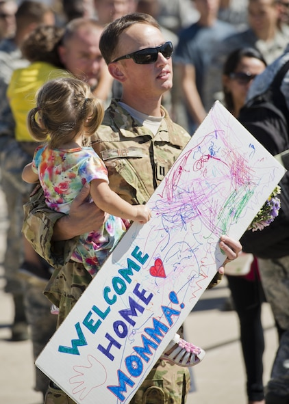 Capt. John Nep, 54th Helicopter Squadron UH-1N evaluator pilot, awaits his wife's return at Minot Air Force Base, N.D., Aug. 29, 2016.  Nep and his daughter waited with other Team Minot families to greet Airmen returning from Andersen Air Force Base, Guam. (U.S. Air Force photo/Airman 1st Class J.T. Armstrong)