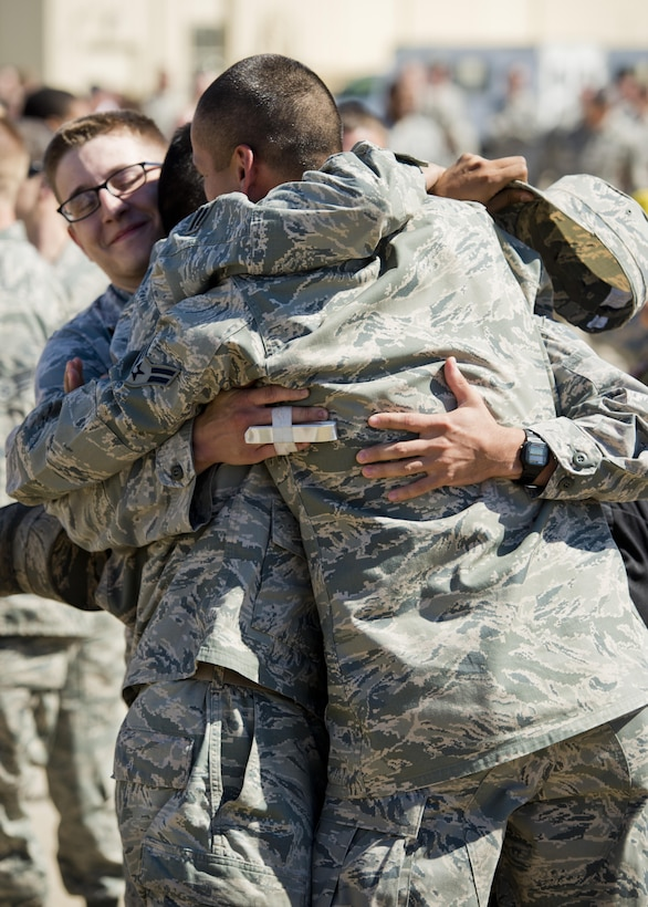 Airmen embrace after returning home from a deployment at Dock 9 at Minot Air Force Base, N.D., Aug. 29, 2016. Airmen from the 5th Bomb Wing were deployed to Andersen Air Force Base, Guam, in support of the continuous bomber presence. (U.S. Air Force photo/Airman 1st Class J.T. Armstrong)
