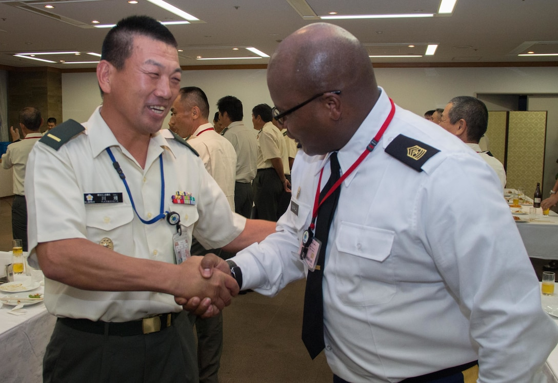 Sgt. Maj. Bennie Nunnally (right), senior enlisted advisor, Army Reserve Engagement Team-Japan, shakes hands with Warrant Officer Himori Kawahata (left), command sergeant major of the Japan Ground Self-Defense Force, during a formal dinner hosted at the Sky View Restaurant in Camp Ichigaya, Japan, Aug. 29, 2016. The JGSDF senior leadership selected approximately 60 Reserve Component service members to Camp Ichigaya to participate in a week-long symposium that promoted esprit de corps between the reserve and active duty component through classroom assignments, field exercises and social events. The JGSDF invited Nunnally to speak about the mission and capabilities of the U.S. Army Reserve and how they enhance the bilateral partnership between Japan and the United States. (U.S. Army photo by Sgt. John Carkeet, U.S. Army Japan)