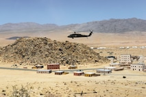 A UH-60 Black Hawk helicopter swoops over a mock city at Fort Irwin's National Training Center. Expeditionary cyber is providing offensive and defensive cyber to the 1st Infantry Division's 1st Armored Brigade Combat Team.