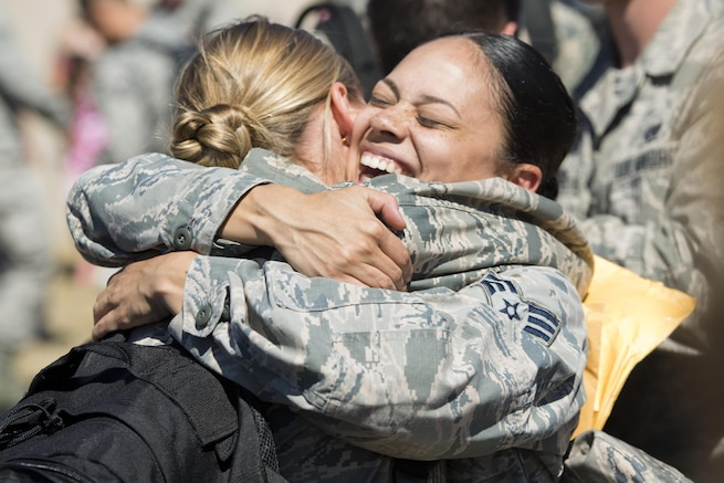 Airmen embrace at Minot Air Force Base, N.D., Aug. 29, 2016, after returning from a deployment. Airmen assigned to the 5th Bomb Wing deployed to Andersen Air Force Base in Guam to help provide continuous bomber presence. Air Force photo by Airman 1st Class J.T. Armstrong