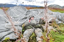 Army Pfc. Oliver Larson pulls on a harness strap after landing during a joint forcible entry exercise onto Malemute drop zone during Exercise Spartan Agoge at Joint Base Elmendorf-Richardson, Alaska, Aug. 23, 2016. Larson is a paratrooper assigned to the 25th Infantry Division's Company H, 1st Battalion, 501st Parachute Infantry Regiment, 4th Brigade Combat Team, Alaska. Air Force photo by Justin Connaher