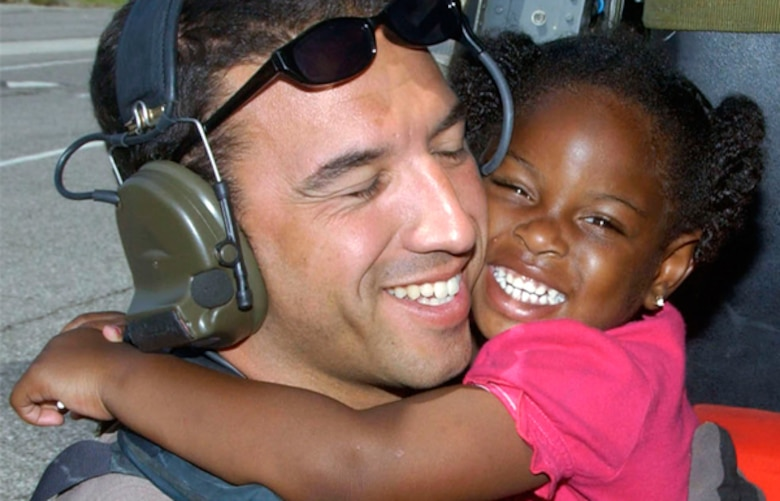 A heartwarming moment depicting the profession of Air Force pararescue which had a prominent role in rescuing victims from the aftermath of Hurricane Katrina 11 years ago. The little girl in a pink shirt and pigtails flung her arms around the neck of Master Sgt. Mike Maroney, pararescueman, who hoisted her from the flooded ruins of her family's New Orleans home. The photo was a positive iconic memento during a dark time, for not only the hurricane victims, but for Maroney who had just returned from an overseas deployment to Afghanistan, before being sent to respond to hurricane victims. (U.S. Air Force photo/Airman 1st Class Veronica Pierce)