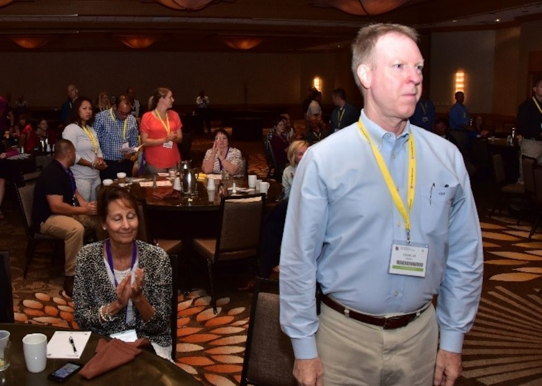 Lt. Col. Charles Powell, 931st Air Reserve Wing flight doctor, McConnell Air Force Base, Kansas, stands while Angeli, his wife, sits behind him clapping as deployers are recognized Aug 26 during a Yellow Ribbon event in Costa Mesa, Ca. (U.S. Air Force photo by Tech. Sgt. Louis Vega Jr.)