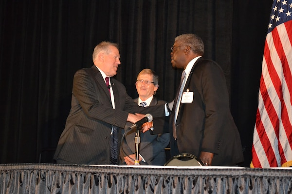 Steve Rodocker (middle), deputy director of DLA Land and Maritime's Strategic Acquisition Programs, and Milton Lewis (right), DLA Land and Maritime acquisition executive, receive a coin of excellence from Frank Kendall, under secretary of defense for acquisition, technology and logistics Aug. 31 at the DLA Land and Maritime Supplier Conference and Expo in Columbus, Ohio.