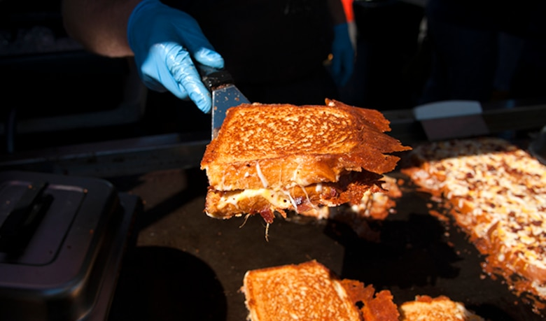 Joe McCarthy, the owner of Meltz Extreme Grilled Cheese, offers up a grilled bacon and cheese sandwich during the Food Truck Festival, Aug. 26, 2016, at Fairchild Air Force Base, Wash. Meltz Extreme Grilled Cheese was one of 10 food trucks to offer free menu samples to all attendees.  (U.S. Air Force photo/Airman 1st Class Ryan Lackey)