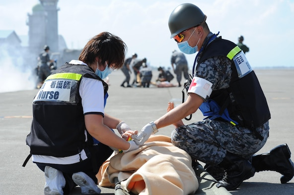 Misawa Hospital nurse, left, and Japan Air Self Defense Force service member check the vitals of a patient during a bilateral emergency management exercise at Misawa Air Base, Japan, Aug. 31, 2016. The exercise prepared USAF and JASDF members to appropriately respond to an improvised explosive device detonation during an air show. (U.S. Air Force photo by Tech. Sgt. April Quintanilla)